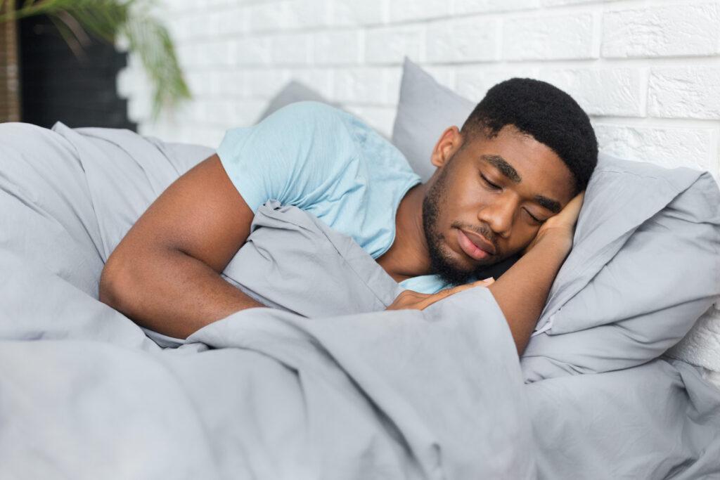 Top Marijuana Strains To Fight Fatigue. Man sleeping in bed,