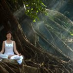 Top Cannabis Strains To Use While Meditating. A woman meditating in a forest.