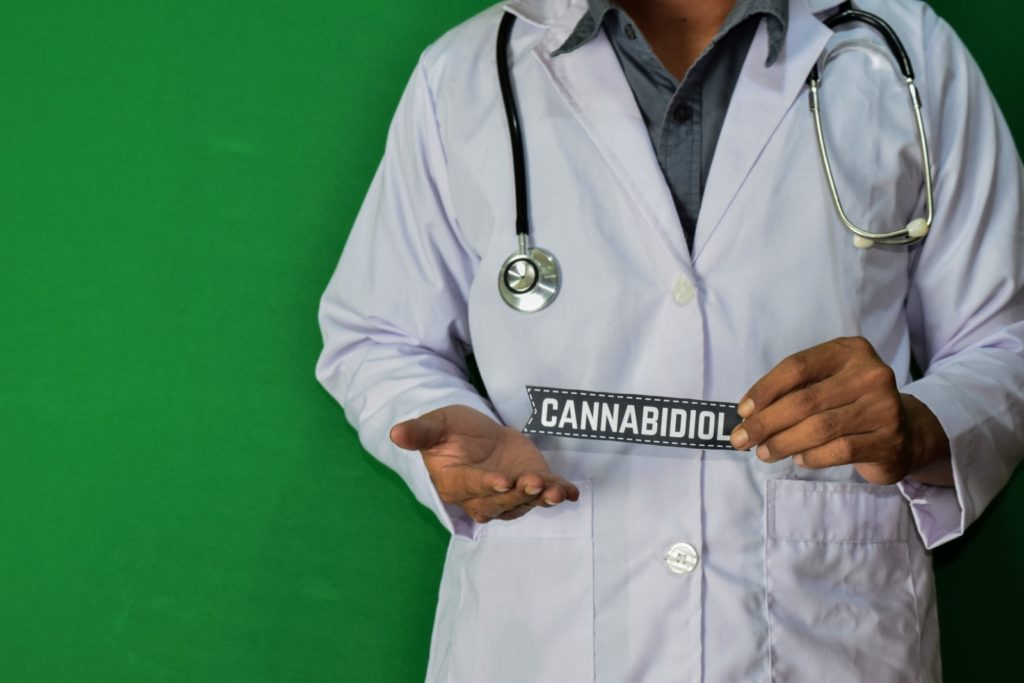 "Build a career in the marijuana industry. A doctor holding a a paper that says ""cannabidiol."""