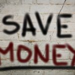 "Smoke weed and save money. ""Save money"" spray painted on a brick wall."