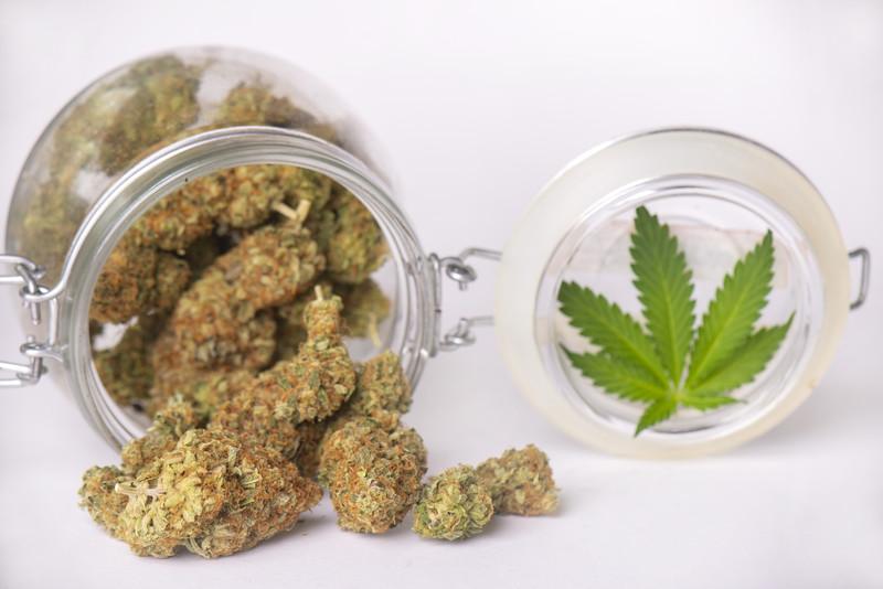 marijuana buds coming out of a glass jar with a marijuana leaf, best marijuana dispensary near me
