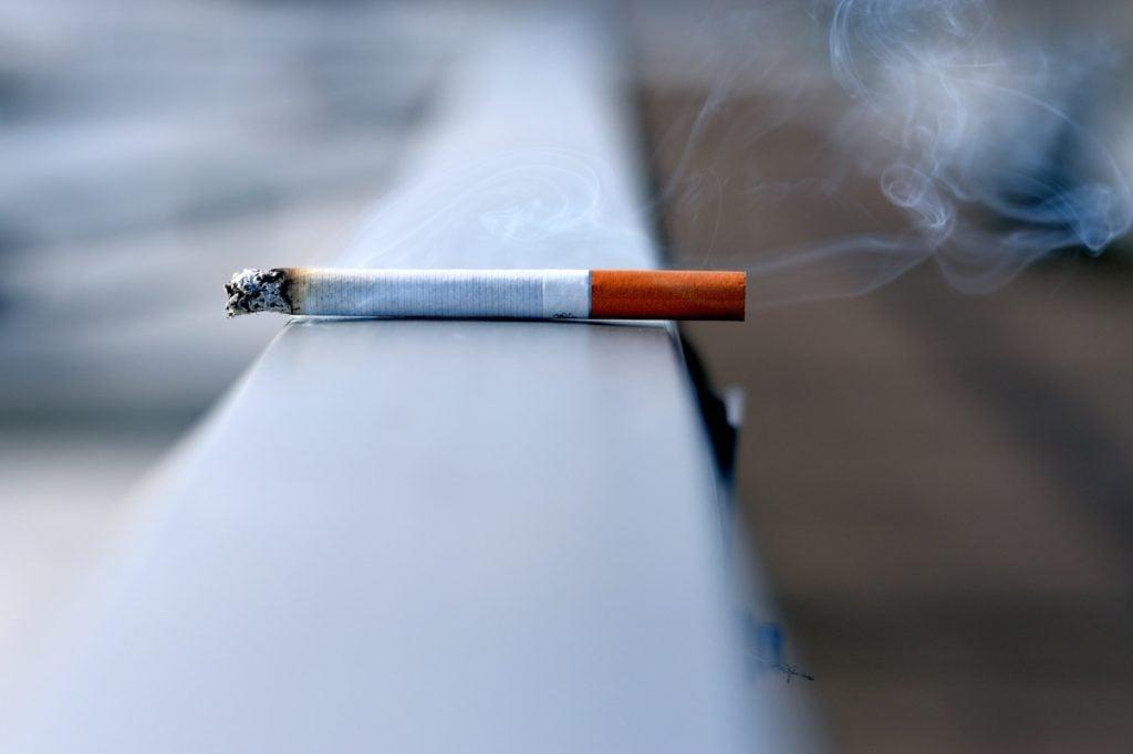 lit cigarette on ledge, CBD helps with cigarette addiction